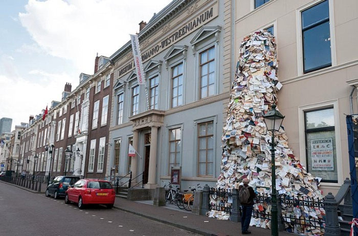 Book sculpture of thousands of books pouring out Museum Meermanno window, by Alicia Martin, contemporary sculpture from Spain