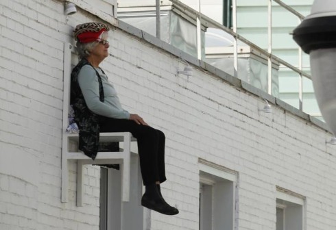 performance art, seniors sitting in chairs hanging from building facades, reading, knitting, sitting. x times people chair, angiel hiesl and roland kaiser