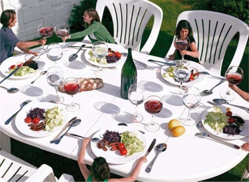 Giant everday objects as art, self-mocking. Giant dinner table, chairs and tablesetting, Gulliver's Dinner, contemporary humorous art